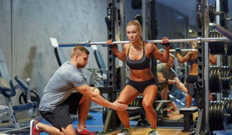 Trainer hilft Frau beim Squats machen