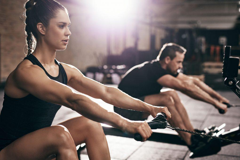 Mann und Frau trainieren an Rudergerät